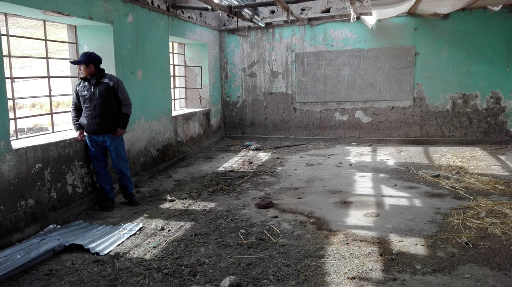 The president of the Huisa community, Juan Magaño, appears among the rubble of what was the area's emblematic school.  Today it is abandoned due to the pollution. Photo: Milagros Salazar.